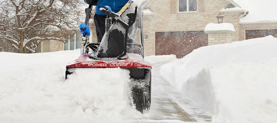 Snow blower clearing a driveway from Markham Mower